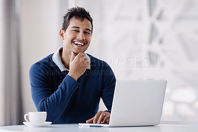 Buy stock photo Cropped portrait of a handsome young businessman looking thoughtful while working on his laptop in the office