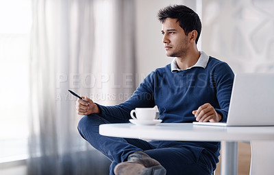 Buy stock photo Cropped shot of a handsome young businessman looking thoughtful while sitting behind his desk in the office