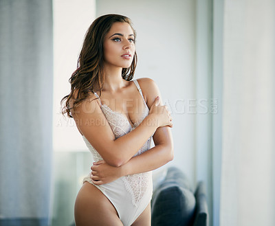 Buy stock photo Shot of a beautiful young woman wearing lingerie in her bedroom at home