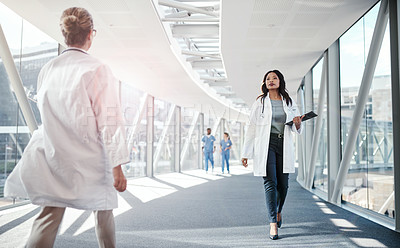 Buy stock photo Shot of a female doctor walking through a hospital
