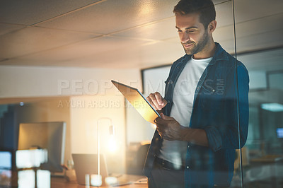 Buy stock photo Shot of a businessman using a digital tablet in his office