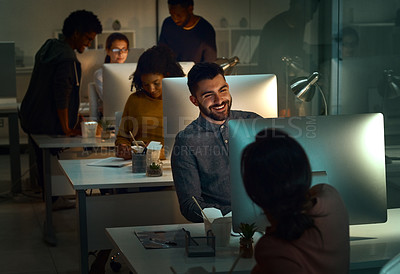 Buy stock photo Shot of a young designer working in an office at night with his colleagues