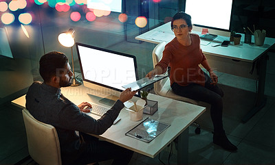Buy stock photo High angle shot of a young designer passing a document to her colleague in an office at night