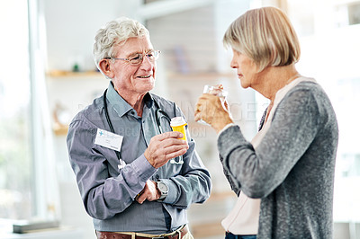 Buy stock photo Shot of a mature doctor giving a senior patient of his medication at a hospital
