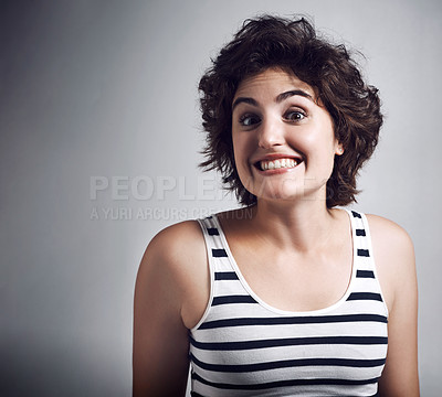 Buy stock photo Studio shot of an attractive young woman grinning broadly while standing against a grey background