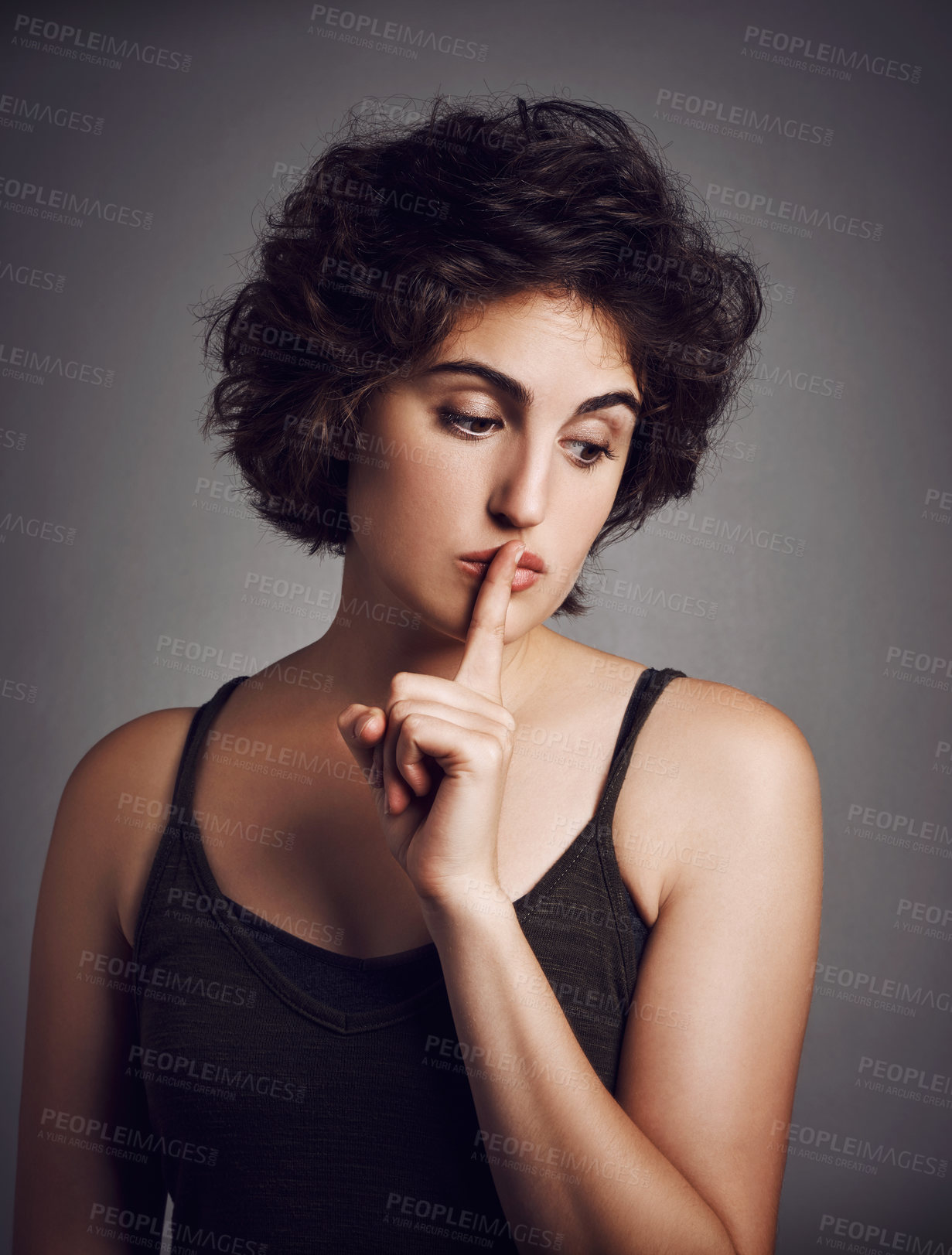 Buy stock photo Studio shot of an attractive young woman with her finger over her lips against a grey background