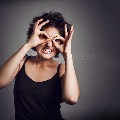 Buy stock photo Studio portrait of an attractive young woman making a funny face while standing against a grey background