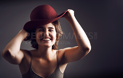 Buy stock photo Stdio shot of an attractive young woman smiling while adjusting her hat against a grey background