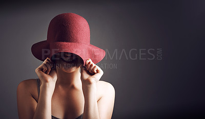 Buy stock photo Studio shot of an unrecognizable young woman covering her face with a hat against a grey background