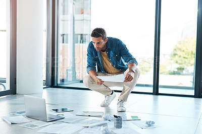 Buy stock photo Shot of a young businessman brainstorming with paperwork on a floor in an office