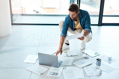 Buy stock photo Shot of a young businessman brainstorming with a laptop and paperwork on a floor in an office