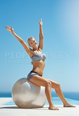 Buy stock photo Full length portrait of an attractive young woman sitting on an exercise ball with her arms raised by the pool