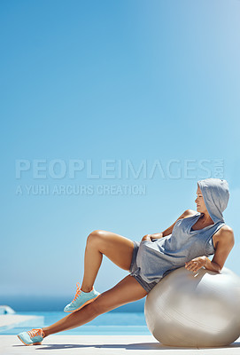 Buy stock photo Full length shot of an attractive young woman leaning against an exercise ball by the pool after her workout