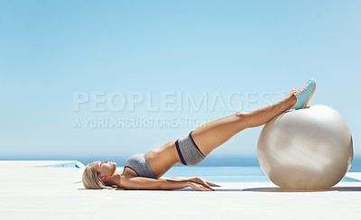 Buy stock photo Full length shot of an attractive young woman working out by the pool with an exercise ball