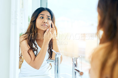 Buy stock photo Cropped shot of a young woman inspecting her skin in the bathroom mirror