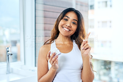Buy stock photo Cropped shot of a beautiful young woman applying moisturizer to her face