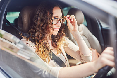 Buy stock photo Shot of an attractive young businesswoman adjusting her spectacles while travelling in her car during the day