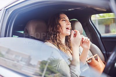 Buy stock photo Shot of an attractive young businesswoman applying lipstick on her mouth while travelling in her car during the day