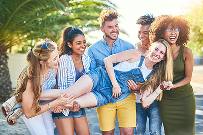 Buy stock photo Cropped shot of a cheerful young woman being held  in the air by her friends outside in the afternoon
