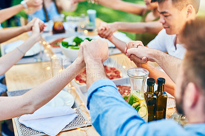 Buy stock photo Cropped shot of a group of cheerful young friends joining hands to say grace at a dinner party outside in the afternoon