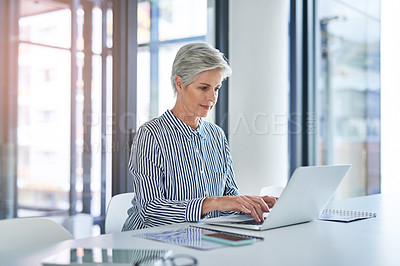 Buy stock photo Shot of an attractive mature businesswoman using a laptop at her office desk at work