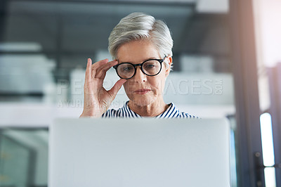 Buy stock photo Shot of an attractive mature businesswoman adjusting her glasses while working on  a laptop in her office