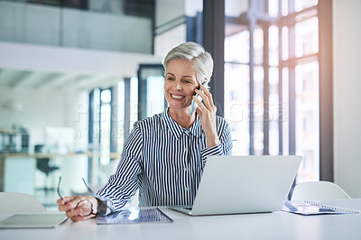 Buy stock photo Shot of an attractive mature businesswoman taking a phone call at her office desk at work