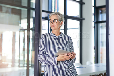 Buy stock photo Shot of an attractive mature businesswoman using a digital tablet in her office