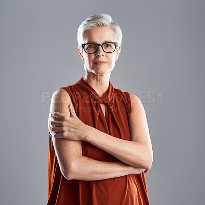 Buy stock photo Portrait of an attractive mature businesswoman posing with her arms folded against a grey background