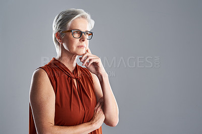 Buy stock photo Shot of an attractive mature woman looking very thoughtful against a grey background