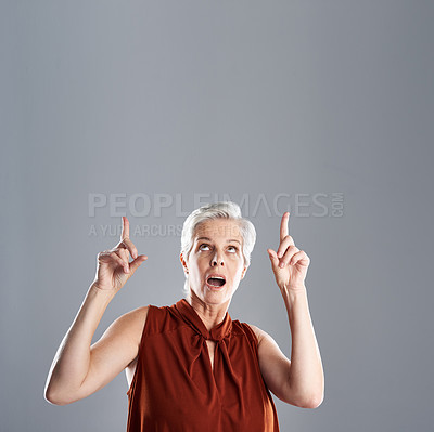 Buy stock photo Shot of a cheerful mature woman looking and pointing up against a grey background