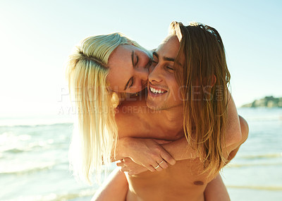 Buy stock photo Shot of a young man giving his girlfriend a piggyback ride at the beach