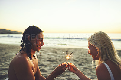Buy stock photo Shot of a happy young couple having fun and lighting sparklers while on a date on the beach at sunset