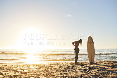 Buy stock photo Full length shot of an unrecognizable young man putting on his wetsuit before going surfing at sunset
