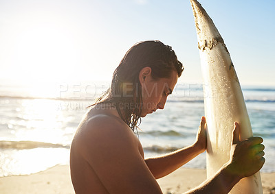Buy stock photo Cropped shot of a handsome young man holding and looking at his surfboard on the beach at sunset