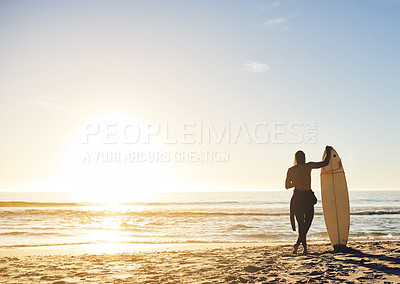 Buy stock photo Rearview shot of an unrecognizable young man holding his surfboard and looking out at the sea at sunset