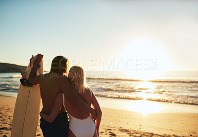 Buy stock photo Cropped rearview shot of an unrecognizable young couple with a surfboard standing and holding each other on the beach