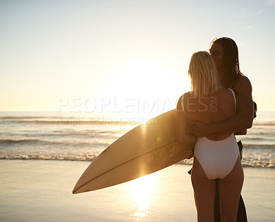 Buy stock photo Cropped shot of an affectionate young couple with a surfboard sharing a tender moment on the beach at sunset