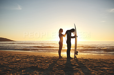 Buy stock photo Full length shot of a young couple zipping up his wetsuit before going surfing at sunset