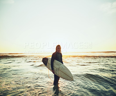 Buy stock photo Portrait of a young man carrying a surfboard at the beach