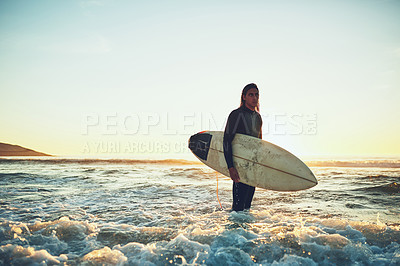 Buy stock photo Shot of a young man carrying a surfboard at the beach