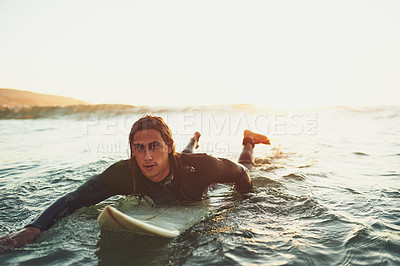 Buy stock photo Portrait of a young man paddling on a surfboard in the sea