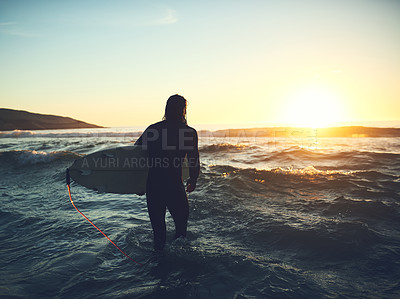 Buy stock photo Rearview shot of a young man carrying a surfboard at the beach