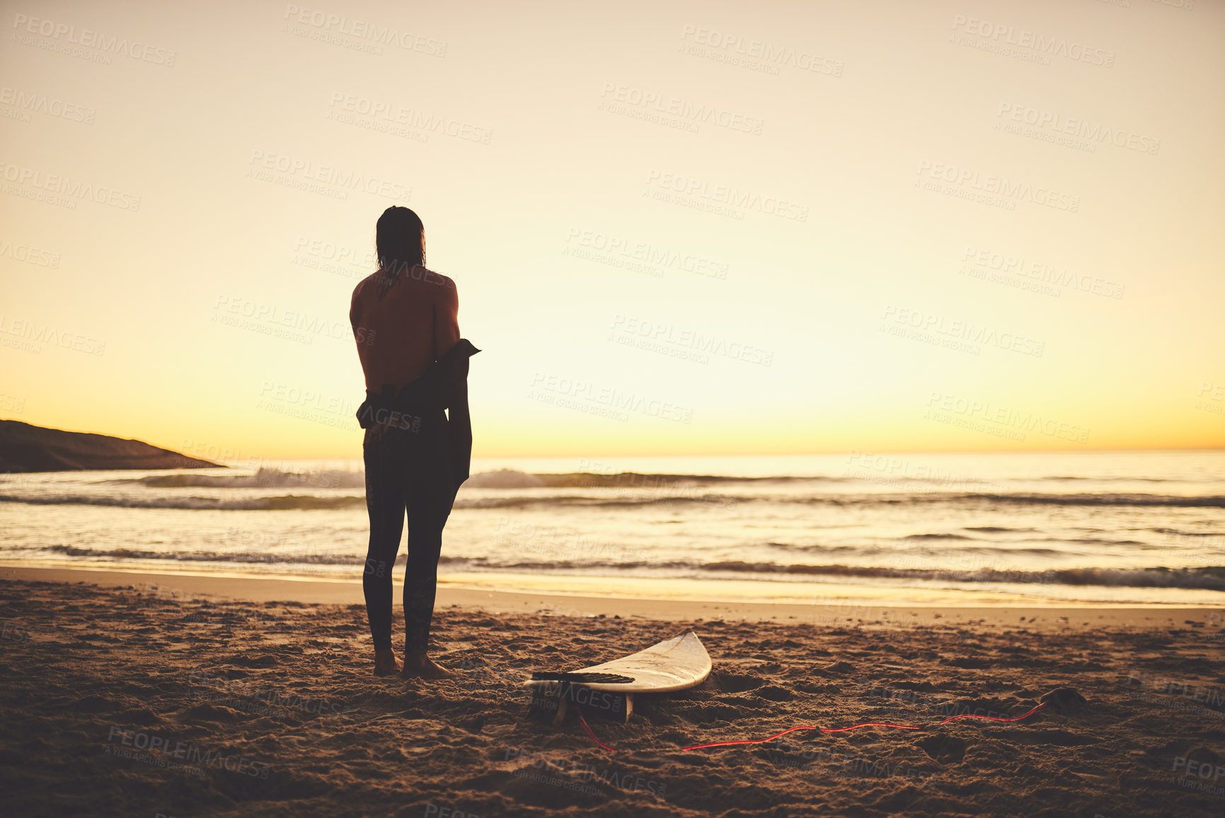 Buy stock photo Rearview of a young surfer putting on a wetsuit at the beach