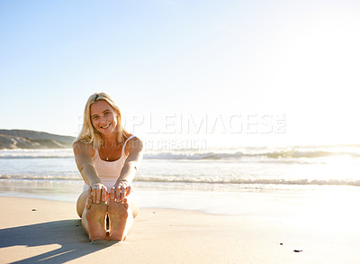 Buy stock photo Full length shot of an attractive young woman in a swimsuit stretching early in the morning on the beach
