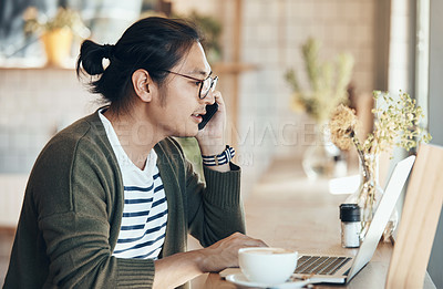 Buy stock photo Shot of a handsome young man working on his laptop and talking on his cellphone in a coffee shop