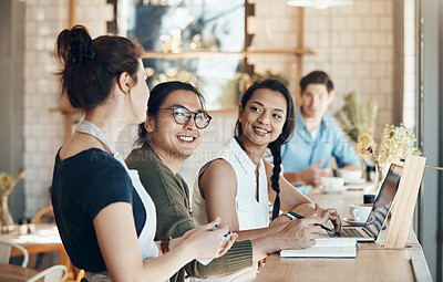 Buy stock photo Shot of a friendly young waitress serving coffee to young business partners in a coffee shop during the day