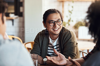 Buy stock photo Shot of a handsome young man sitting and smiling with his friends in a coffee shop during the day