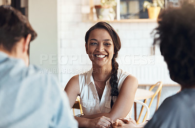 Buy stock photo Shot of an attractive young woman sitting and smiling with her friends in a coffee shop during the day