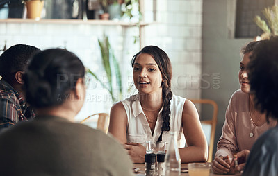 Buy stock photo Shot of a diverse young group sitting together in a coffee shop during the day